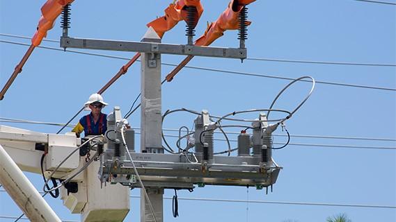 fpl worker in a bucket truck working on a power line
